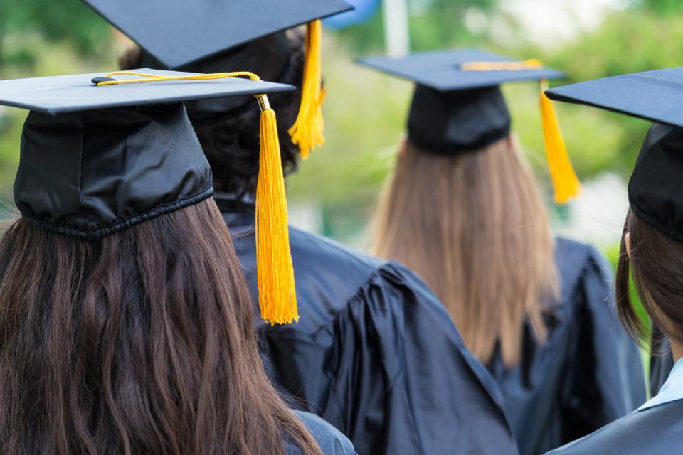 High school or college graduates walking across lawn