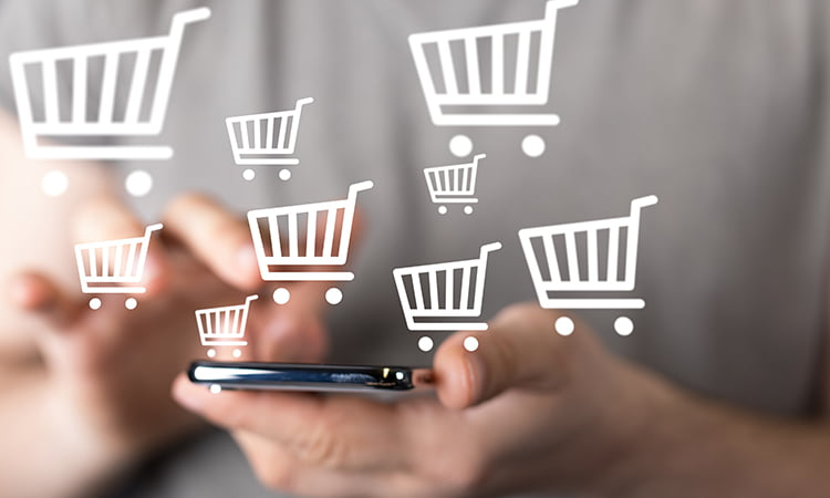 A photo of a woman holding a cell phone with cartoon shopping carts surrounding her hands.