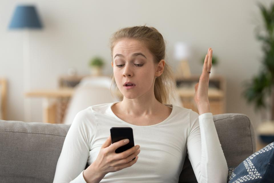 Annoyed young woman looking at smartphone having problem with phone