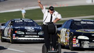 Actor and comedian Kevin James celebrates while racing NASCAR stock cars with his Segway to promote the release of his new movie,