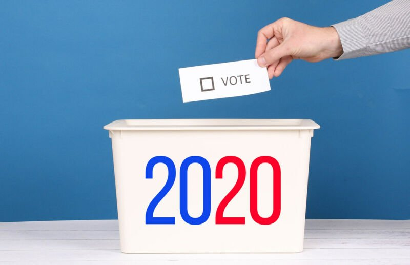 Stock photo of a slip of paper being dropped into a bin marked 2020.
