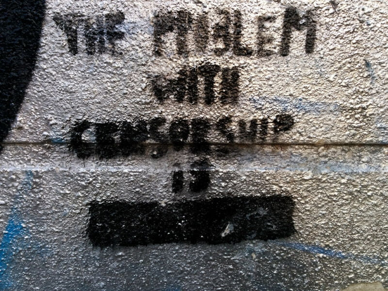 A pithy phrase regarding censorship has been spray painted on a wall: the problem with censorship is redacted.
