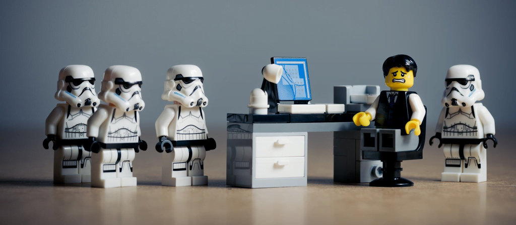 LEGO stormtroopers surrounding someone at a desk